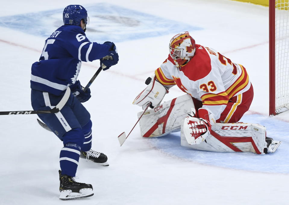 Calgary Flames goaltender David Rittich (33) makes a save against Toronto Maple Leafs right wing Ilya Mikheyev (65) on a breakaway during second-period NHL hockey game action in Toronto, Monday, Feb. 22, 2021. (Nathan Denette/The Canadian Press via AP)