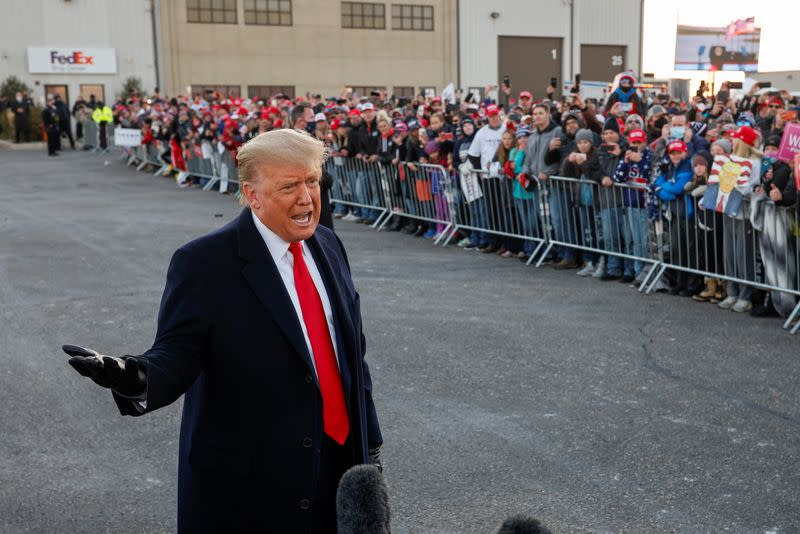 U.S. President Donald Trump talks to the media as Trump supporters gather in Rochester