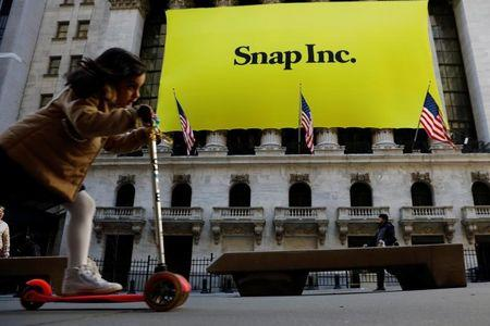 A young girl pushes her scooter past the front of the New York Stock Exchange (NYSE) with a Snap Inc. logo hung on the front of it shortly before the company's IPO in New York