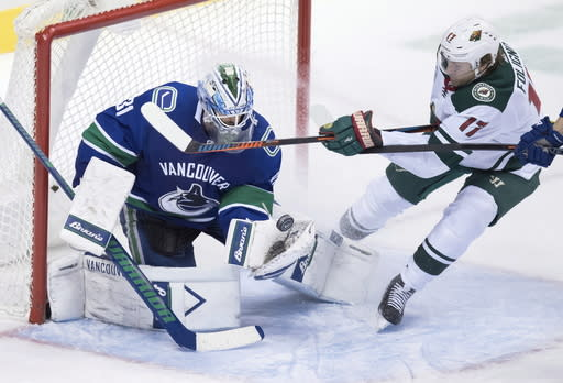 Vancouver Canucks goalie Anders Nilsson, left, of Sweden, makes the save as Minnesota Wild's Marcus Foligno attempts to get his stick on the puck during the second period of an NHL hockey game, Tuesday, Dec. 4, 2018, in Vancouver, British Columbia. (Darryl Dyck/The Canadian Press via AP)
