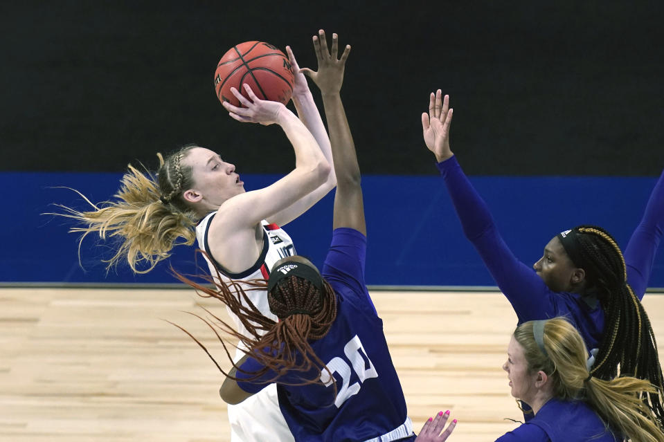 FILE - UConn guard Paige Bueckers, left, drives to the basket against High Point during the first half of a college basketball game in the first round of the women's NCAA tournament at the Alamodome in San Antonio, in this Sunday, March 21, 2021, file photo. Paige Bueckers is in a class all by herself. UConn's star guard became the first freshman ever to win The Associated Press women's basketball player of the year award Wednesday, March 31, 2021. (AP Photo/Eric Gay, File)