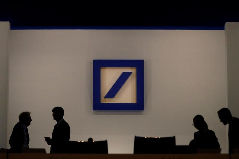 FILE PHOTO: People are silhouetted next to the Deutsche Bank's logo prior to the bank's annual meeting in Frankfurt