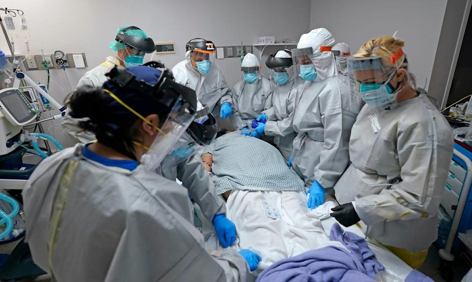 Dr. Joseph Varon, top with JV on shield, leads a team as they tried without success to save the life of a patient inside the Coronavirus Unit at United Memorial Medical Center, Monday, July 6, 2020, in Houston.