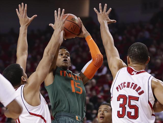 Miami's Rion Brown (15) shoots over Nebraska's Tai Webster, left, and Walter Pitchford (35) in the first half of an NCAA college basketball game in Lincoln, Neb., Wednesday, Dec. 4, 2013. (AP Photo/Nati Harnik)