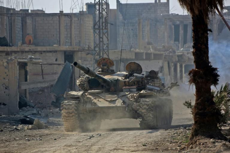 A Syrian army tank rolls into the formerly rebel-held area of Beit Nayem in Eastern Ghouta on March 6, 2018