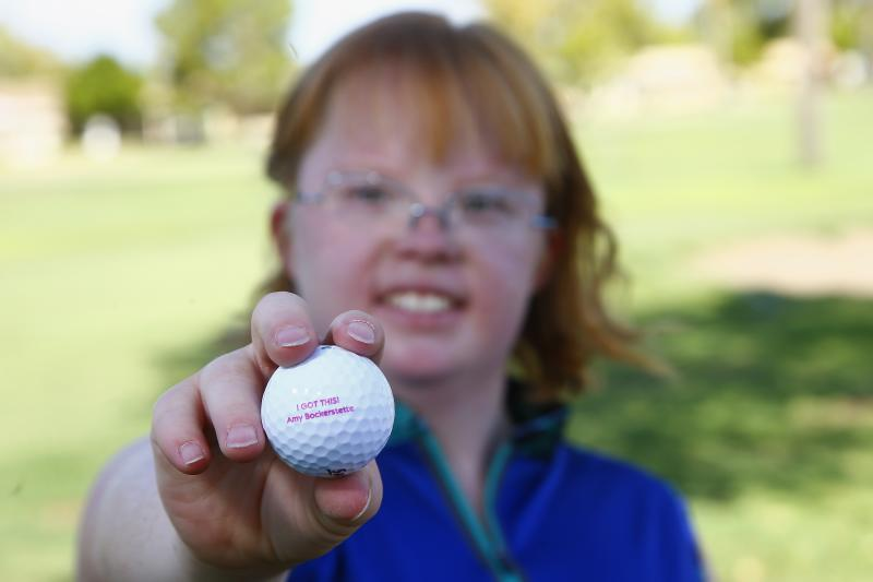 In this Aug. 28, 2019, photo, Amy Bockerstette, the golfer with Down syndrome who was an internet sensation by making par at the 16th hole at the Phoenix Open with soon-to-be 2019 U.S. Open champion Gary Woodland, smiles as she holds up a personalized logo golf ball after her golf lesson at Palmbrook Country Club in Sun City, Ariz. (AP Photo/Ross D. Franklin)