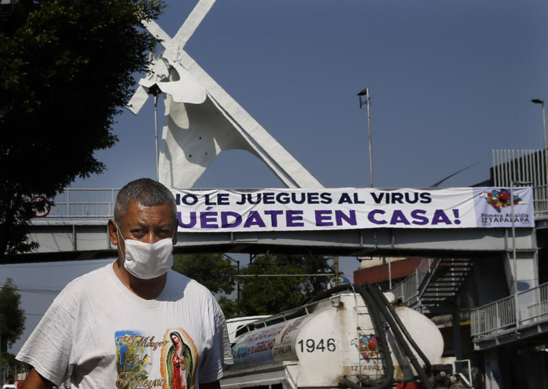 "A man walk past a banner that reads in Spanish ""Don't play with your life. Stay home,"" as he wears a mask against the spread of the new coronavirus in Mexico City, Thursday, April 9, 2020. The Mexico City government is sending out teams to help the home-bound and the homeless during the shutdown declared to combat the coronavirus. (AP Photo/Marco Ugarte)"