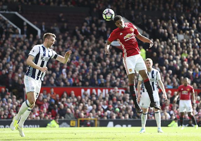 <p>Manchester United's Marcus Rashford, right, jumps for a high ball with West Bromwich Albion's Gareth McAuley, left, during their English Premier League soccer match at Old Trafford in Manchester, England </p>
