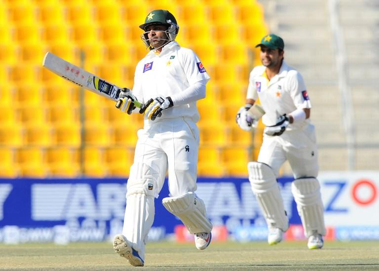Pakistan batsmen Mohammad Hafeez (L) and Ahmed Shehzad (R) run between the wickets during the final day of the first cricket Test match between Pakistan and Sri Lanka at the Sheikh Zayed Stadium in Abu Dhabi on January 4, 2014. AFP PHOTO/Ishara S. KODIKARA