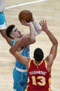 Charlotte Hornets guard LaMelo Ball (2) shoots as Atlanta Hawks guard Bogdan Bogdanovic (13) defends during the first half of an NBA basketball game Wednesday, Jan. 6, 2021, in Atlanta. (AP Photo/John Bazemore)