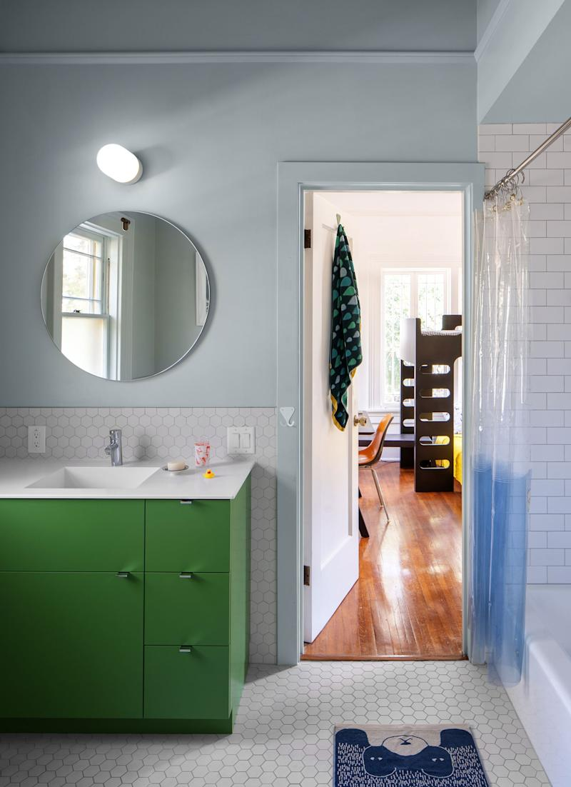 The kids' Jack-and-Jill-style bathroom has larger format hexagonal tiles that recalls traditional hexagonal tiles from the 1920s, but with a playful twist. The walls are painted Sea Salt.