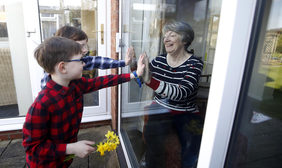 Ben and Isaac talk to their grandmother Sue through a window, as she and her husband Alan self-isolate due at their home in Knutsford, Cheshire. (Photo by Martin Rickett/PA Images via Getty Images)