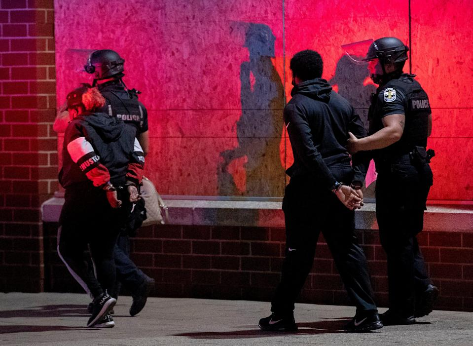 Police lead detained protesters to the Louisville Metro Department of Corrections on Wednesday, Sept. 23, 2020, in downtown Louisville, Kentucky.