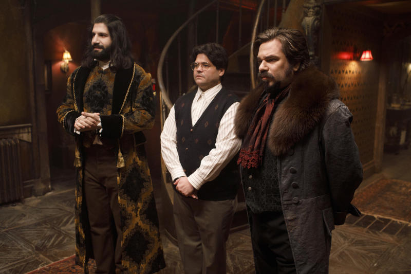 """This image released by FX shows Kayvan Novak, form left, Harvey Guillen and Matt Berry in a scene from """"What We Do In the Shadows."""" The series premiering Wednesday is based on the 2014 cult-hit movie from New Zealand. (John P Johnson/FX via AP)"""