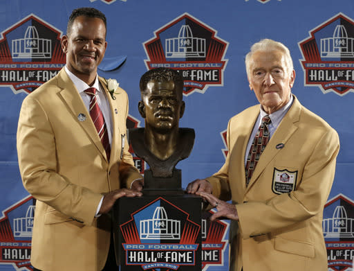 Hall of Fame inductee Andre Reed, left, and presenter Marv Levy pose with the bust during the 2014 Pro Football Hall of Fame Enshrinement Ceremony at the Pro Football Hall of Fame Saturday, Aug. 2, 2014, in Canton, Ohio. (AP Photo/Tony Dejak)