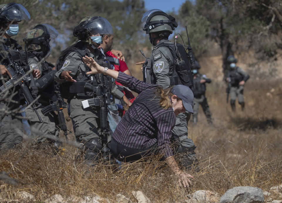 Israeli border police pushes a Palestinian woman while dispersing journalists and farmers using stun grenades and teargas, in the West Bank village of Burqa, East of Ramallah, Friday, Oct. 16, 2020. Palestinians clashed with Israeli border police in the West Bank on Friday during their attempt to reach and harvest their olive groves near a Jewish settlers outpost. (AP Photo/Nasser Nasser)