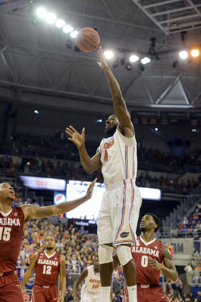 Florida center Patric Young (4) shoots over Alabama forward Nick Jacobs (15) during the first half of an NCAA college basketball game Saturday, Feb. 8, 2014, in Gainesville, Fla.(AP Photo/Phil Sandlin)