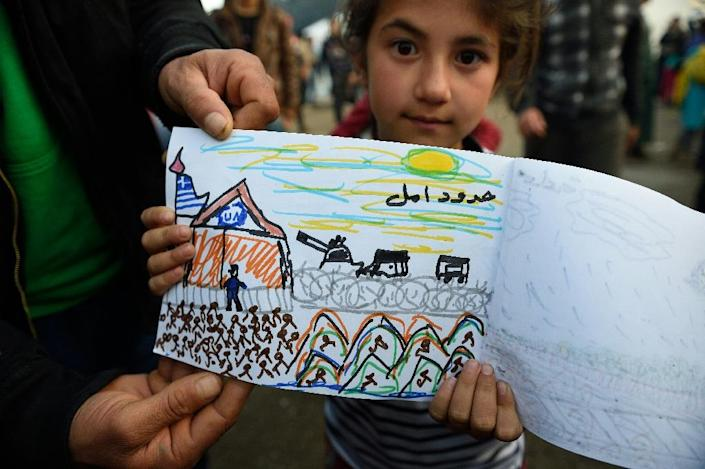 8-year-old Schecherezade from Aleppo, Syria shows her drawings displaying her experiences during the exodus from her country in a makeshift camp at the Greek-Macedonian border (AFP Photo/Daniel Mihailescu)