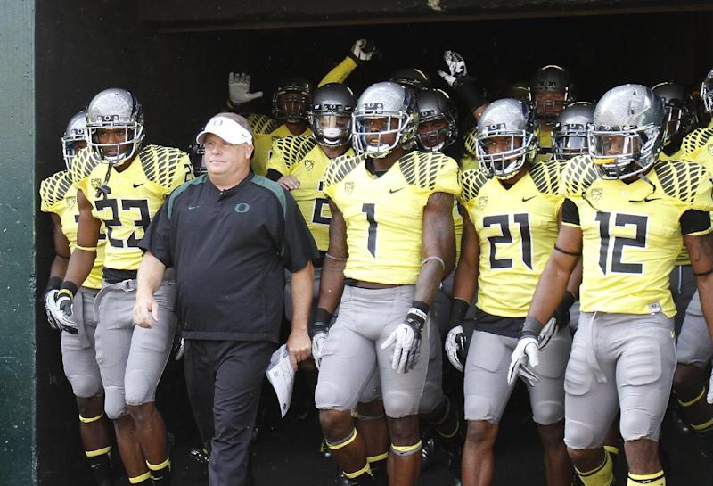 """FILE - In this Sept. 8, 2012 file photo, Oregon football coach Chip Kelly walks out of the tunnel with his team before their NCAA college football game against Fresno State in Eugene, Ore. The University of Oregon proposed a self-imposed two-year probation and the loss of a scholarship for three years because of possible recruiting violations involving the Ducks' football program. The university released documents late Monday, April 15, 2013 that included a proposed summary disposition from September which discusses the violations and characterizes at least one as """"major."""" Kelly was head coach of the Ducks for the past three seasons. He left Oregon to become head coach of the Philadelphia Eagles earlier this year.  (AP Photo/Don Ryan, File)"""