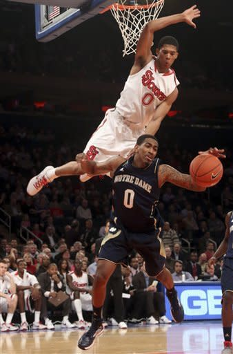 St. John's Jamal Branch, top, fouls Notre Dame's Eric Atkins during the first half of an NCAA college basketball game, Tuesday, Jan. 15, 2013, at Madison Square Garden in New York