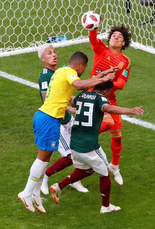 <p>Mexico's Guillermo Ochoa punches the ball clear of Brazil's Casemiro REUTERS/David Gray </p>
