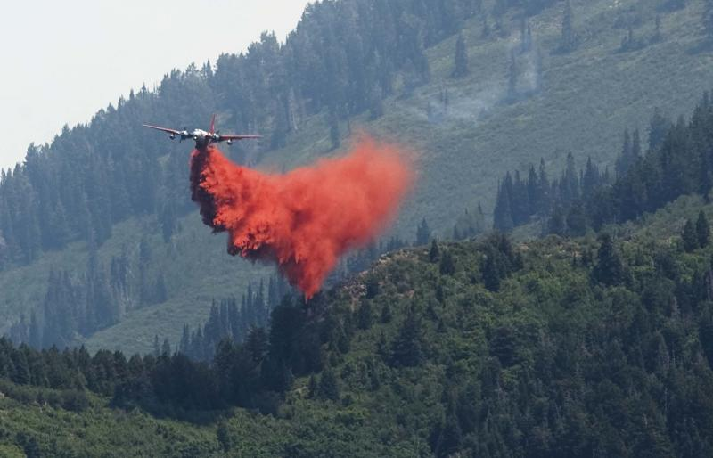 A tanker filled with fire retardant makes a drop on the north end of the fire in Alpine, Utah in Wednesday, July 4, 2012. Firefighters lifted some evacuation orders and called in two hot-shot crews to help battle a still-uncontrolled Utah County wildfire Wednesday. 350 homes remained under mandatory evacuation orders as firefighters fought the nearly 2,900-acre blaze, aided by winds blowing the blaze back up the ridge, away from houses. (AP Photo/The Salt Lake Tribune, Leah Hogsten)