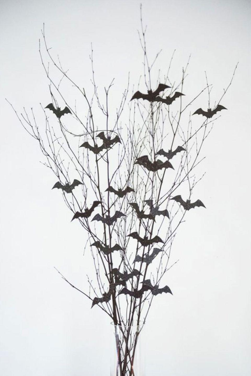 """<p>Give your table a spooky feel with this easy-to-make arrangement. Plus, you can save money on this DIY by foraging your backyard for branches and twigs.</p><p><strong>Get the tutorial at <a href=""""http://thesweetestoccasion.com/2016/10/diy-halloween-centerpiece/"""" rel=""""nofollow noopener"""" target=""""_blank"""" data-ylk=""""slk:The Sweetest Occasion"""" class=""""link rapid-noclick-resp"""">The Sweetest Occasion</a>.</strong></p><p><strong><a class=""""link rapid-noclick-resp"""" href=""""https://www.amazon.com/Halloween-Fntacetik-Decorations-Window-Stickers/dp/B07H6X84SR/ref=sr_1_2?tag=syn-yahoo-20&ascsubtag=%5Bartid%7C10050.g.3739%5Bsrc%7Cyahoo-us"""" rel=""""nofollow noopener"""" target=""""_blank"""" data-ylk=""""slk:SHOP BAT CUTOUTS"""">SHOP BAT CUTOUTS</a></strong> </p>"""