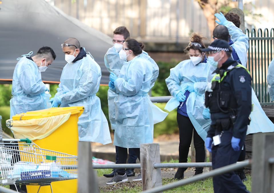 Medical workers and police are seen at a Government Commission tower in North Melbourne which remains under strict lockdown in Melbourne, Saturday, July 18, 2020. Victoria recorded 428 coronavirus cases on Friday, the highest daily increase since the start of the pandemic. (AAP Image/David Crosling) NO ARCHIVING