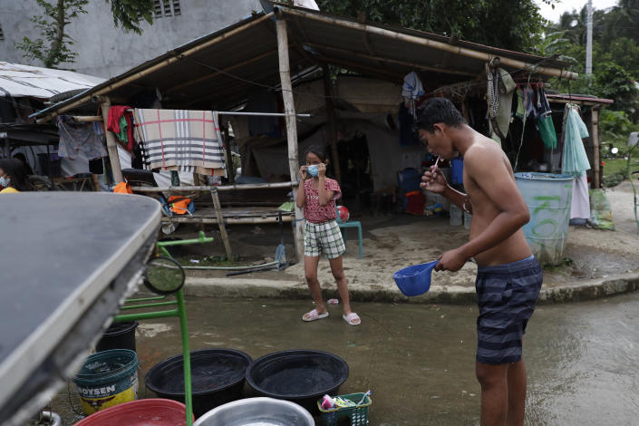 John Paulo Silva, a former resident at Taal volcano, brushes his teeth outside their tent at a relocation site in Balete, Batangas province, Philippines, Sunday, Jan. 10, 2021. Some families are still living in tents and have resorted to taking odd jobs to make a living as the government has prevented them from returning back to their homes almost a year after Taal volcano erupted on Jan. 12, 2020. The eruption displaced thousands of villagers living near the area and delivered an early crisis this year for one of the world's most disaster-prone nations a couple of months before the COVID-19 pandemic broke in the country. (AP Photo/Aaron Favila)