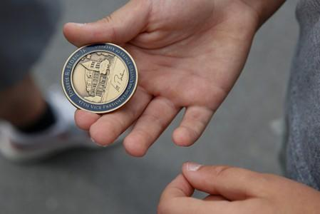 A boy holds out a challenge coin given to him by Democratic 2020 U.S. presidential candidate and former Vice President Joe Biden outside Lindy's Diner in Keene