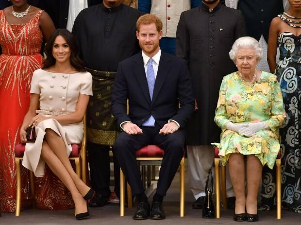 Queen Elizabeth, Prince Harry and Meghan, the Duchess of Sussex, pose for a picture at a Buckingham Palace reception following the final Queen's Young Leaders Awards ceremony in London on June 26, 2018. Both Meghan and Harry spoke warmly of the Queen during the interview Sunday night.