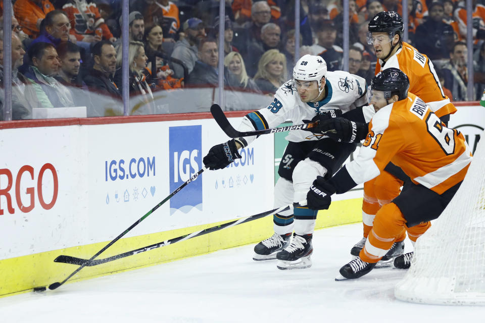 San Jose Sharks' Timo Meier (28) tries to keep the puck away from Philadelphia Flyers' Justin Braun (61) and Robert Hagg (8) during the first period of an NHL hockey game, Tuesday, Feb. 25, 2020, in Philadelphia. (AP Photo/Matt Slocum)