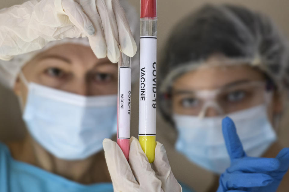 People in protective suits and face masks look at test tubes with samples of the vaccine against the coronavirus. (Photo illustration by Maxym Marusenko/NurPhoto via Getty Images)