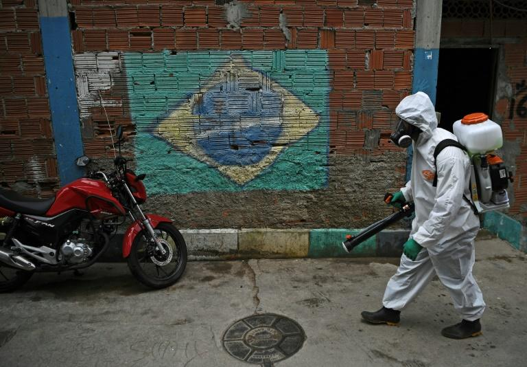 A volunteer walks past a mural of the Brazilian flag in April 2020 as he disinfects an area in Rio de Janeiro in the souteast of Brazil, which is the only region in the country worse-hit from the coronavirus than the northeast