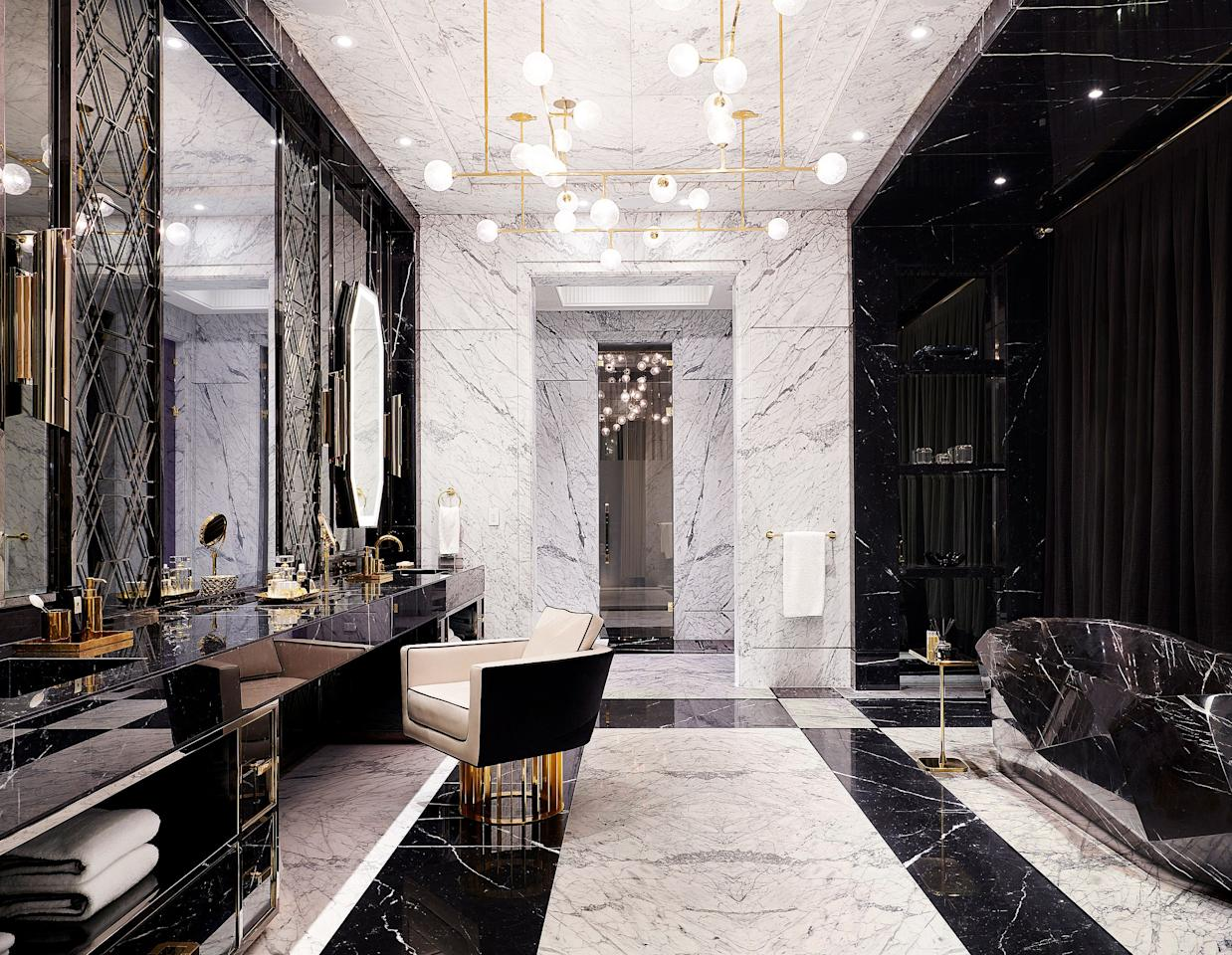 "The master bath features a Nero Marquina marble vanity and tub. Custom chandelier by <a href=""https://www.lumifer.us/"">Lumifer</a>; <a href=""https://www.brabbu.com/home/"">Brabbu</a> sconces; chair by <a href=""http://ferrisrafauli.com/"">Rafauli</a>."
