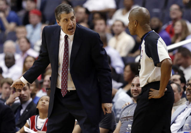 Washington Wizards coach Randy Wittman discusses a call with referee Sean Corbin during the second half of an NBA basketball game against the Milwaukee Bucks, Saturday, April 12, 2014, in Washington. The Wizards won 104-91. (AP Photo/Alex Brandon)
