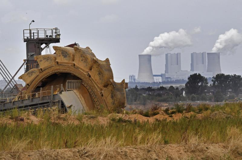 FILE - In this Aug. 27, 2018 file photo a bucket wheel digs for coal near the Hambach Forest near Dueren, Germany. Germany's greenhouse gas emissions fell sharply last year, putting the country's 2020 climate goal within reach again. The state governors Dietmar Woidke of Brandenburg, Michael Kretschmer of Saxony, Reiner Haseloff of Saxony-Anhalt and Armin Laschet of North Rhine-Westphalia meet in Berlin for the adoption by the Bundestag and Bundesrat of the laws on coal phase-out and structural strengthening in the affected federal states. (AP Photo/Martin Meissner)