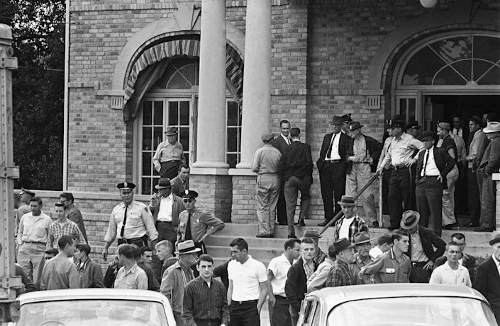 """An angry crowd mills around outside the City Hall in McComb, Miss., Dec. 1, 1961, after several """"Freedoms Riders"""" arrived on a bus and left in a private car. The crowd vented their anger on newsmen and photographers and police took them into the building."""