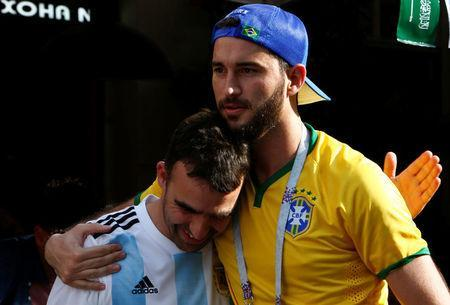 A Brazil fan embraces a supporter of Argentina soccer team as he celebrates Brazil's victory over Costa Rica at the World Cup Group E soccer match in central Moscow, Russia June 22, 2018. REUTERS/Sergei Karpukhin
