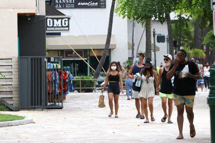 People walk past shops in the Waikiki neighborhood of Honolulu, Tuesday, Aug. 24, 2021. Hawaii was once seen as a beacon of safety during the pandemic because of stringent travel and quarantine restrictions and overall vaccine acceptance that made it one of the most inoculated states in the country. But the highly contagious delta variant exploited weaknesses as residents let down their guard and attended family gatherings after months of restrictions and vaccine hesitancy lingered in some Hawaiian communities.(AP Photo/Caleb Jones)