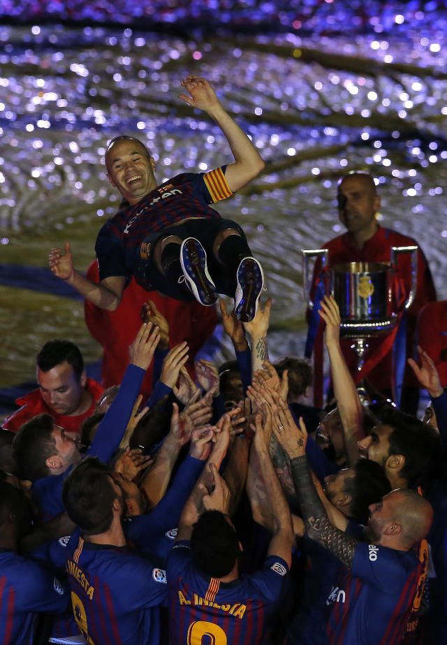 FC Barcelona's Andres Iniesta is tossed by his teammates after the Spanish La Liga soccer match between FC Barcelona and Real Sociedad at the Camp Nou stadium in Barcelona, Spain, Sunday, May 20, 2018. Iniesta announced last month he would leave Barcelona after 16 seasons. (AP Photo/Manu Fernandez)
