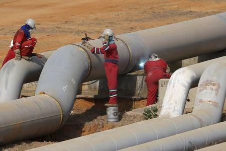 Oil workers weld a new pipeline at PDVSA's Jose Antonio Anzoategui industrial complex in the state of Anzoategui April 15, 2015.  REUTERS/Carlos Garcia Rawlins