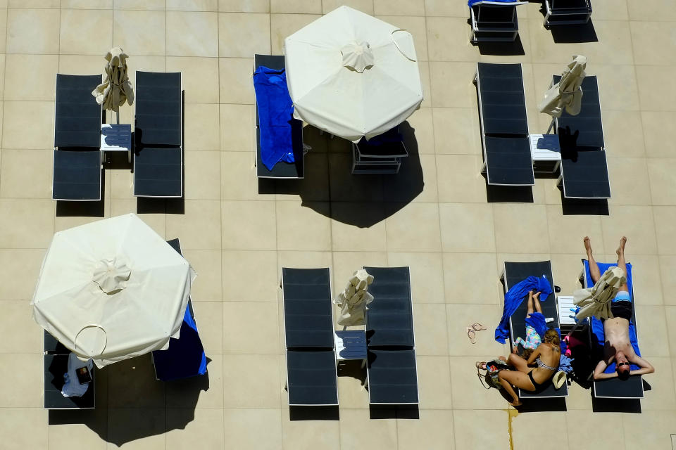 A family enjoy their vacations at the pool of Nissi Blue hotel in southeast resort of Ayia Napa, in the eastern Mediterranean island of Cyprus, Saturday, May 22, 2021. Cypriot hotel and other tourism-related business owners say they'd like to see the COVID-19 pandemic-induced uncertainty over travel bookings to the tourism-reliant island nation winding down by July when they're hoping authorities in Cyprus' main markets including the U.K., Russia, Germany and the Scandinavian countries will make it easier for their citizens to travel abroad. (AP Photo/Petros Karadjias)