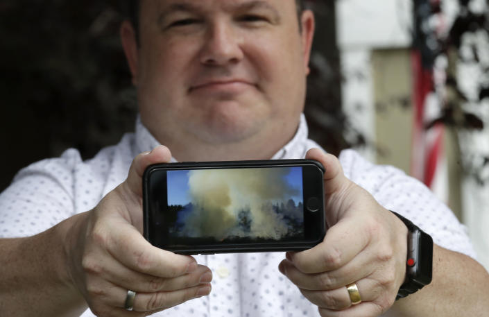 In this photo taken Friday, Aug. 2, 2019, Jason Ritchie holds his phone with a photo he took of a wildfire behind his home four years earlier, in Sammamish, Wash. (AP Photo/Elaine Thompson)