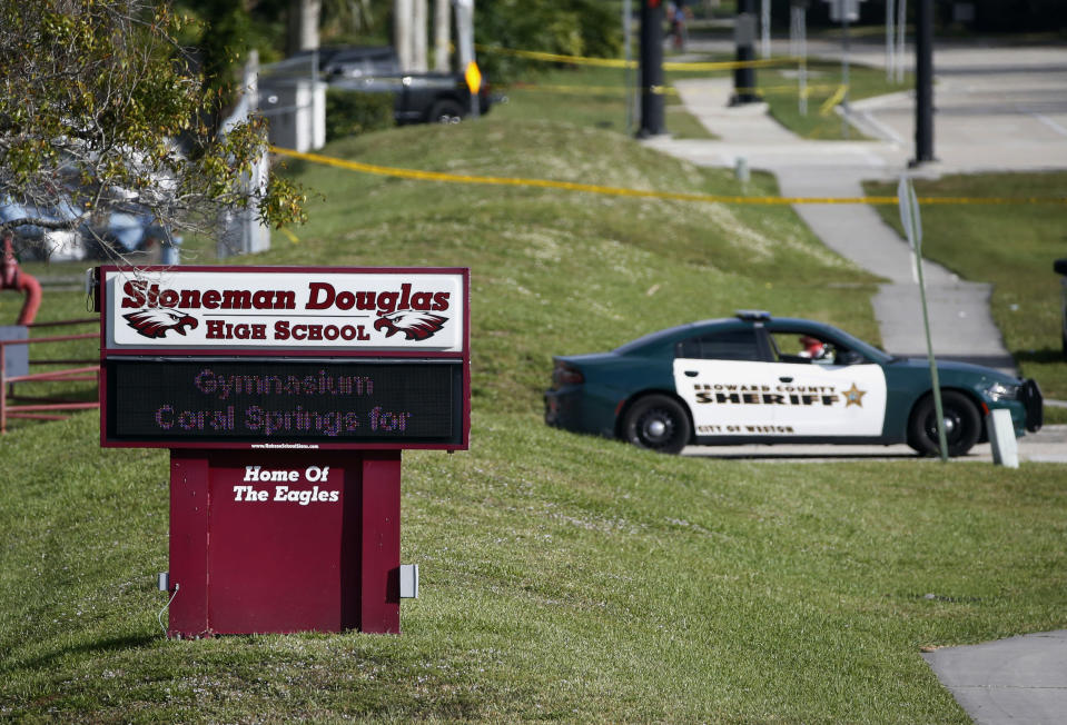 FILE- In this Feb. 15, 2018, file photo, law enforcement officers block off the entrance to Marjory Stoneman Douglas High School in Parkland, Fla., following a deadly shooting at the school. Sorrow is reverberating across the country Sunday, Feb. 14, 2021, as Americans joined a Florida community in remembering the 17 lives lost three years ago in the Parkland school shooting massacre. President Joe Biden used the the occasion to call on Congress to strengthen gun laws, including requiring background checks on all gun sales and banning assault weapons. (AP Photo/Wilfredo Lee, File)