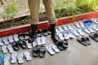 A guard stands on inmates shoes, while the prisoners pray, during an inspection visit inside Klong Prem high-security prison in Bangkok, Thailand July 12, 2016. REUTERS/Jorge Silva
