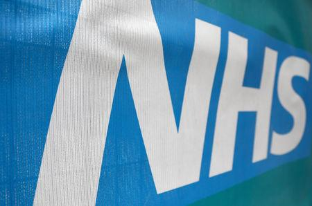 FILE PHOTO: An NHS logo is displayed outside a hospital in London