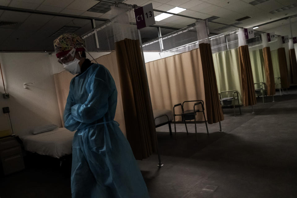 Registered traveling nurse Patricia Carrete, of El Paso, Texas, walks down the hallways during a night shift at a field hospital set up to handle a surge of COVID-19 patients, Wednesday, Feb. 10, 2021, in Cranston, R.I. Rhode Island's infection rate has come down since it was the highest in the world two months ago and many of the field hospital's 335 beds are now empty. On quiet days, the medical staff wishes they could do more. (AP Photo/David Goldman)