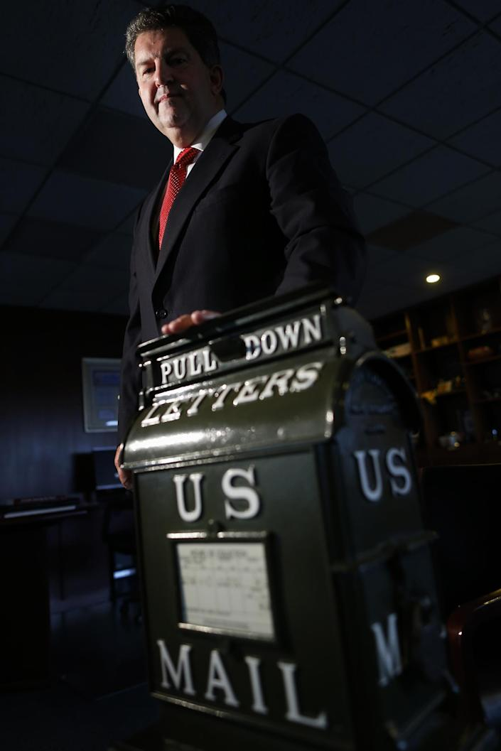 Postmaster General Patrick R. Donahoe poses with a mailbox from the early 1900's after he was interviewed by the Associated Press at his office at U.S. Postal Service Headquarters in Washington, Thursday, Aug. 1, 2013. Donahoe has a wish list for raising cash for his financially ailing agency. High on it is delivery of beer, wine and spirits. In an interview with The Associated Press, Donahoe also endorsed ending most door-to-door and Saturday mail deliveries as cost-saving measures. (AP Photo/Charles Dharapak)