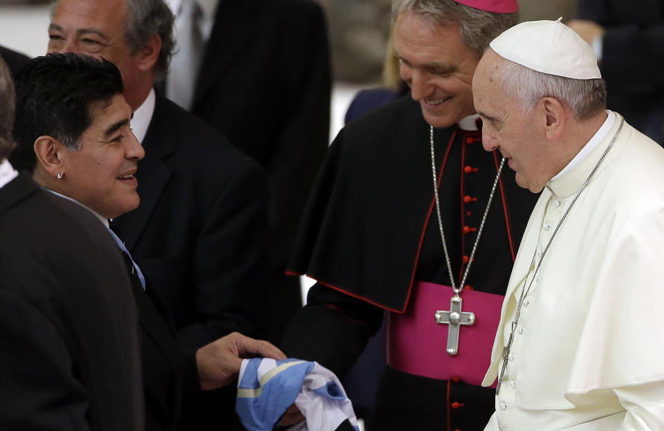 FILE -- In this Sept. 1, 2014 file photo, Argentine soccer legend Diego Armando Maradona, left, greets Pope Francis in the Paul VI hall at the Vatican. Diego Maradona says he's Pope Francis' top fan. The Argentine soccer great who was among the best players ever and who led his country to the 1986 World Cup title died from a heart attack on Wednesday, Nov. 25, 2020, at his home in Buenos Aires. He was 60. (AP Photo/Gregorio Borgia, File)